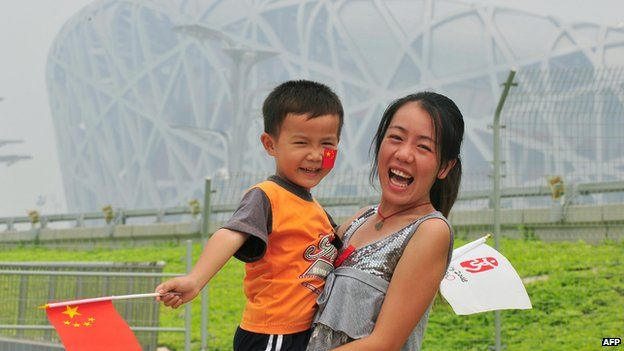 Chinese tourists pose outside the Olympic Bird's Nest Stadium in Beijing on 10 September, 2012