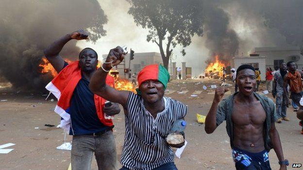 Men shout slogans in front of burning cars, near the Burkina Faso's parliament - 30 October 2014, Ouagadougou, Burkina Faso