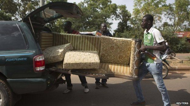 People carry a couch looted from the house belonging to Francois, younger brother of Burkina Faso's ex-President Blaise Compaore, in Ouagadougou, capital of Burkina Faso, 31 October 2014