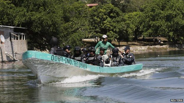 Federal police on a boat search a river for 43 missing student teachers on 30 October, 2014.
