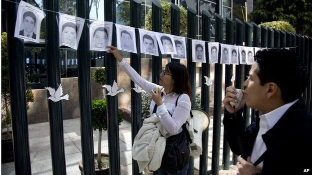 Students read aloud the names of the missing 43 rural college students, whose images were strung on the front gate of the Mexican attorney general's office in Mexico City on 29 October, 2014