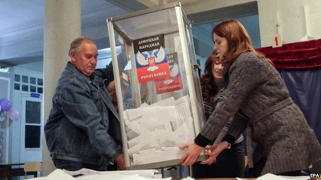 Members of an electoral commission empty a ballot box to count votes at the end of elections at a polling station in Donetsk