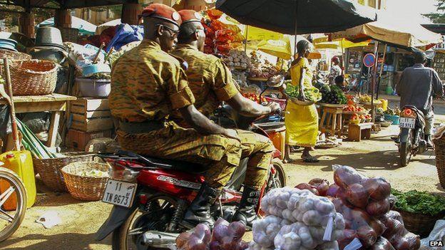Soldiers ride a motorcycle through a market in Ouagadougou. Photo: 5 November 2014