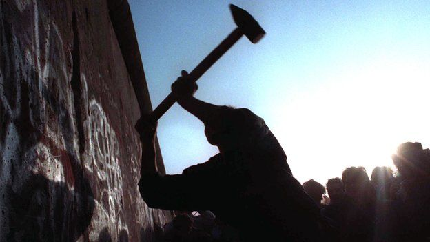 A man takes a hammer to the Berlin Wall