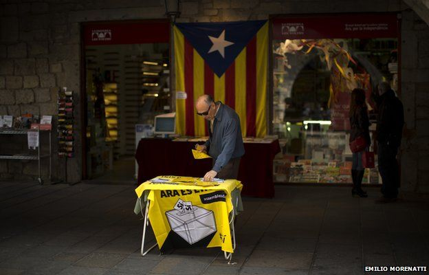 A man looks at information on a table about an informal poll scheduled for next Sunday in a street in Girona, Spain, on Saturday Nov. 8, 2014