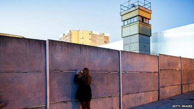 """A visitor peeks into the former """"death strip"""" between layers of the former Berlin Wall next to a former East German guard tower at the Berlin Wall Memorial at Bernauer Strasse. 8 Nov 2014"""