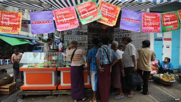 This photo taken on 1 August 2014 shows people buying Ooredoo mobile phone SIM cards from a shop in Yangon.
