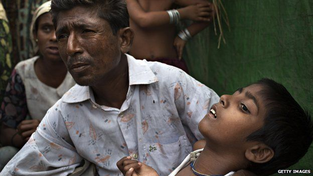 Roshida Moud, 12, is held by his father as he explains that his son was hit in the head with a stone during the Rakhine violence