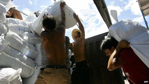 Labourers unload a shipment of slippers at Guanlei Port in Xishuangbanna Dai Autonomous Prefecture which borders Myanmar and Laos