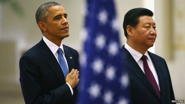 US President Barack Obama (L) and China's President Xi Jinping listen to national anthems behind a US flag during a welcoming ceremony at the Great Hall of the People in Beijing, 12 November 2014