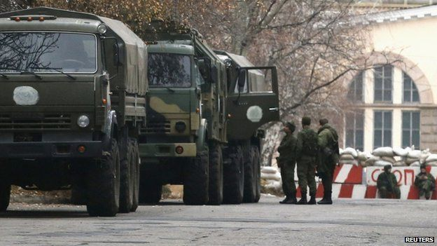Armed people and military trucks are seen near a checkpoint outside a building on the territory controlled by the self-proclaimed Donetsk People's Republic in Donetsk,