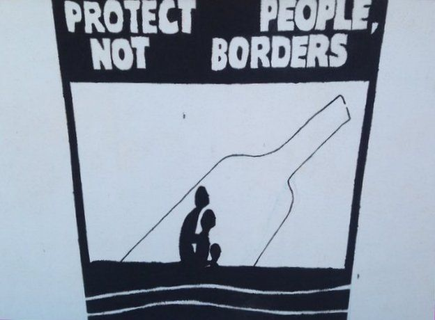 """A painting """"Protect people not borders"""" outside the mayor's office in Lampedusa"""