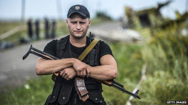 Armed separatist guarding the crash site