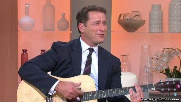 Karl Stefanovic wearing the blue suit, holding a guitar