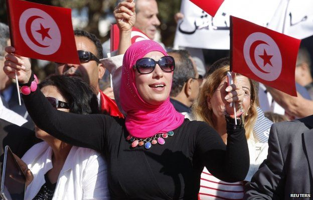 A supporter of Beji Caid Essebsi, Nidaa Tounes party leader and presidential candidate, waves flags and shouts slogans during the opening of his campaign headquarters in Monastir November 2, 2014.