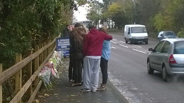 People crying and hugging as they leave flowers on the ground