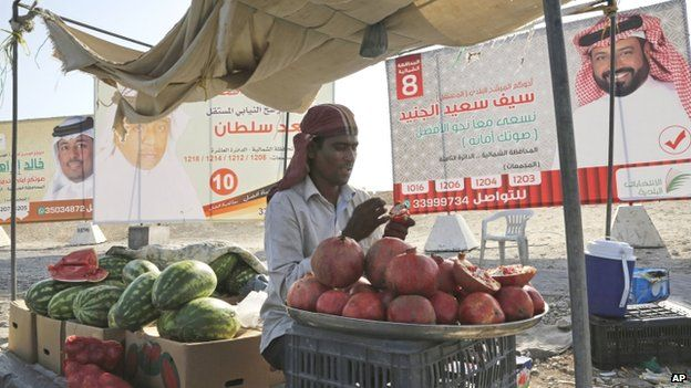 An Asian vendor waits for costumers in front of a election campaign posters of Saif Saeed al Jeneed, right, Saad Sultan, centre, and Khalid Ibrahim, left, in Hamad Town, Bahrain