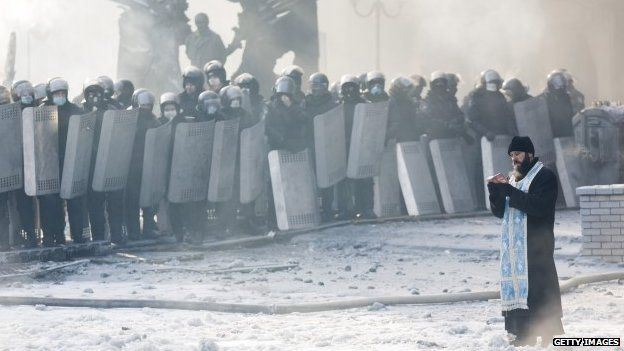 An Orthodox priest prays between police and protesters at the scene of anti-government protests in Kiev (January 2014)