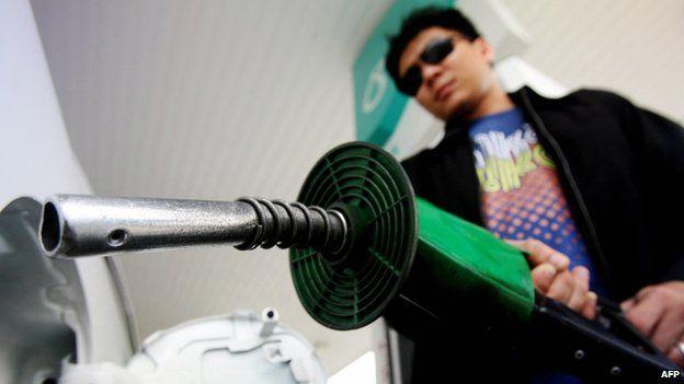 A man replaces a petrol pump at a Petronas station