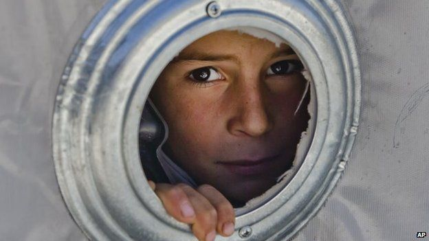 A Syrian Kurdish refugee child from the Kobane area looks through a ventilation hole of a tent at a camp in Suruc, on the Turkey-Syria border, 19 November 2014
