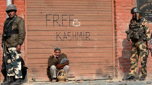 Indian paramilitary soldiers look on as a Kashmiri resident leans against a shuttered storeroom for a smoke in Tral.