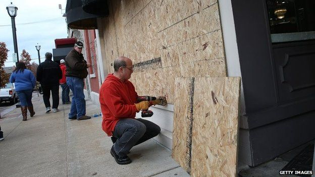 Workers board up windows at a restaurant near the Buzz Westfall Justice Center in Clayton, Missouri, 24 November 2014