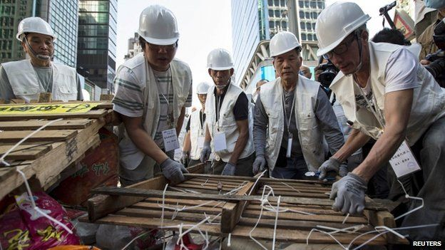 Workers dismantle a barricade at a small section in the Mongkok protest site after a court issued an eviction order in Hong Kong November 25, 2014.