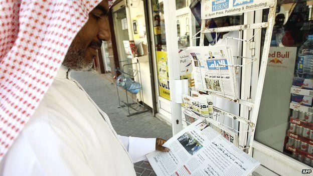Man reading newspaper in Bahrain