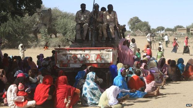 A picture taken during a government-organised tour shows Sudanese troop standing guard near villagers in Tabit, in the North Darfur, on 20 November 2014