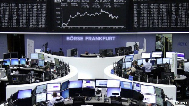 Traders at their desks in front of the German share price index DAX board at the Frankfurt stock exchange (25 November 2014)