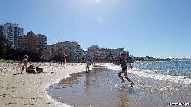Children enjoy the weather on a beach in Sydney
