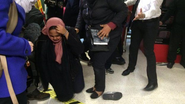 A woman on her knees, having fallen over in a supermarket