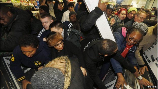 """Shoppers compete to purchase retail items on """"Black Friday"""" at an Asda superstore in Wembley"""