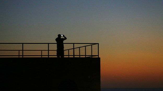 A man takes a picture with his mobile phone