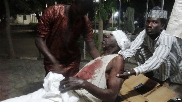 People assist an injured man in Kano. Photo: 28 November 2014