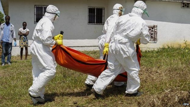 Liberian Red Cross team retrieves the body of a suspected victim of Ebola near Monrovia on 24 October, 2014