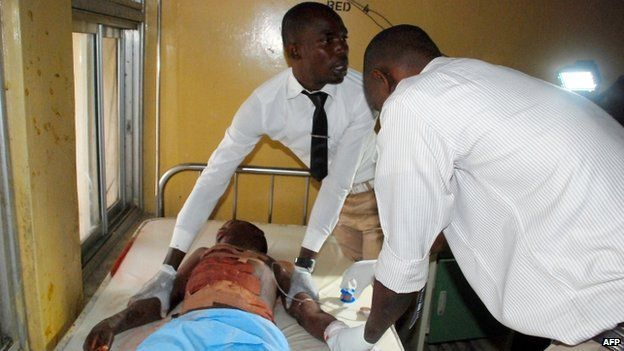 Medical officers attend to a man injured following double female suicide bomb attacks that killed nearly 80 people in Maiduguri, north-eastern Nigeria on 25 November 2014