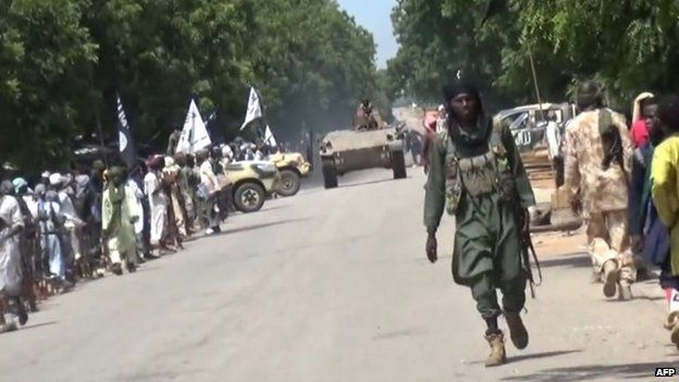 Sceengrab taken on 9 November 2014 from a new Boko Haram video obtained by AFP shows a militant parading with a tank in an unidentified town in north-eastern Nigeria