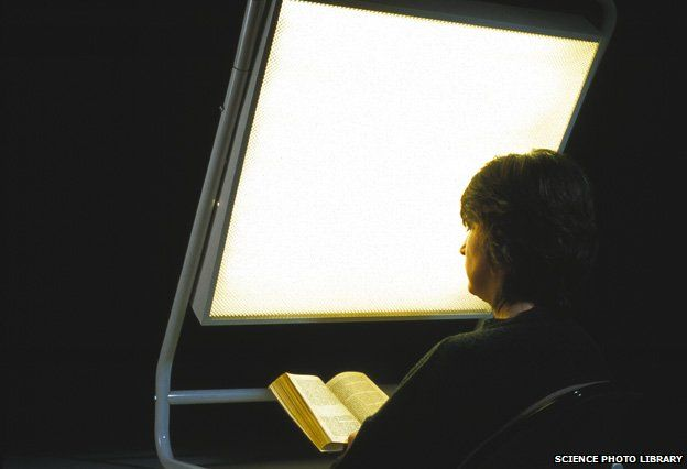 Woman reading a book as she undergoes phototherapy in front of a light screen