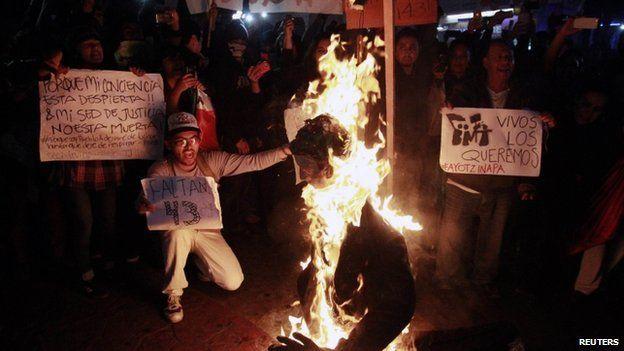 Protestors burn effigy of the president
