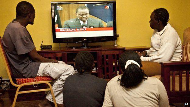Kenyans watch national television in Nairobi, as Kenyan President Uhuru Kenyatta, addresses the nation