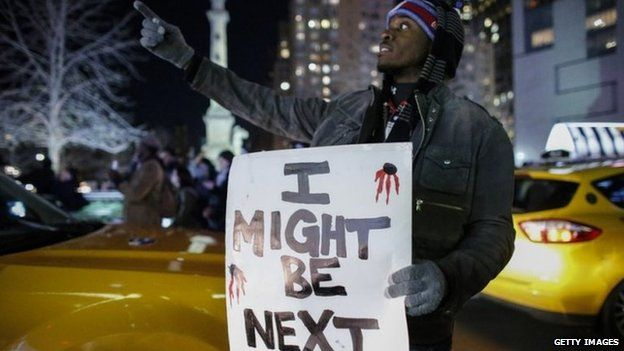 A man holds a sign as he takes part in a protest in New York after a grand jury decided not to indict New York Police Officer Daniel Pantaleo in Eric Garner's death on 3 December