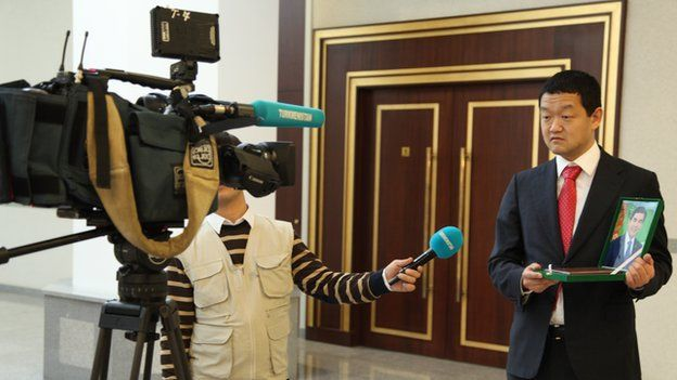 Conference delegate holds portrait of Turkmen president for TV cameras (Nov 2014)