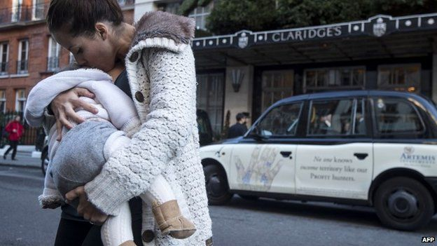 Woman breastfeeds her baby outside Claridge's