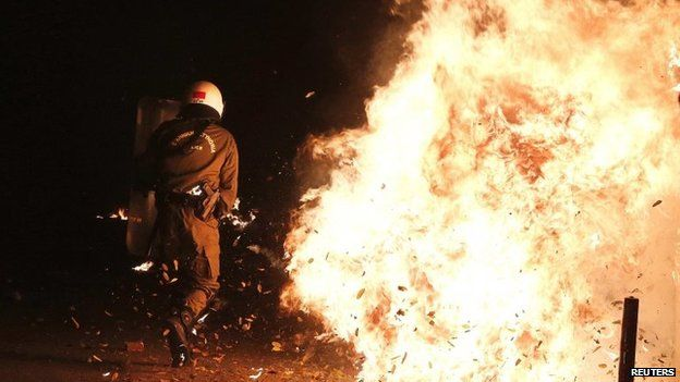 Riot policemen dodge a petrol bomb during clashes in central Athens, 6 December 2014