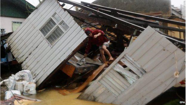 Man climbs over fallen building in Borongan city, Samar island (7 Dec 2014)