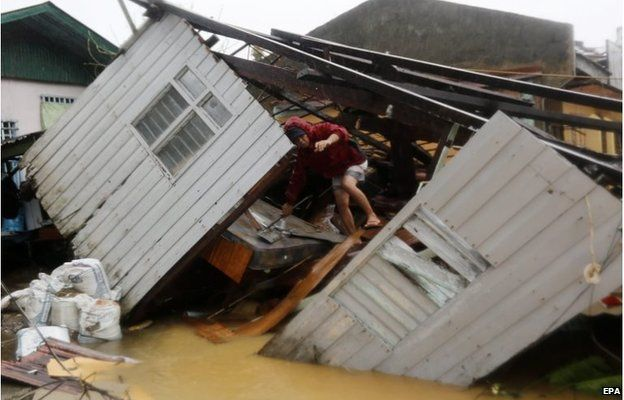 Man climbs over ruined building in Borongan City, Philippines (7 Dec 2014)