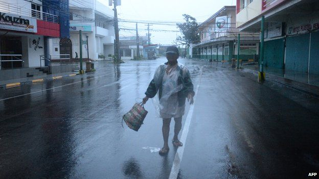 A resident braves strong wind and rain as he heads to the market, hours before Typhoon Hagupit passes near the city of Legazpi on December 7, 2014.