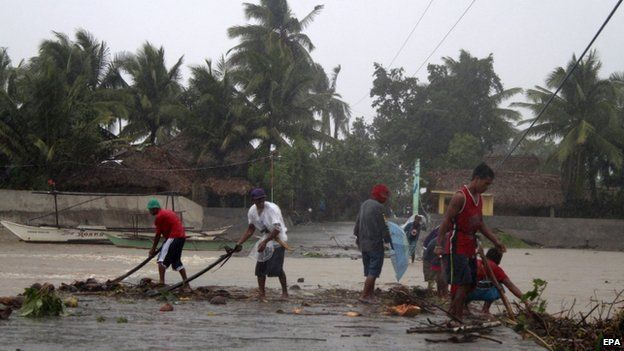 Filipinos clear the debris along the flooded street in Sorsogon City, Bicol region, south of Manila, Philippines, 7 December 2014