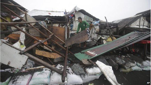 Man clears a ruined building in Borongan City, Philippines (7 Dec 2014)
